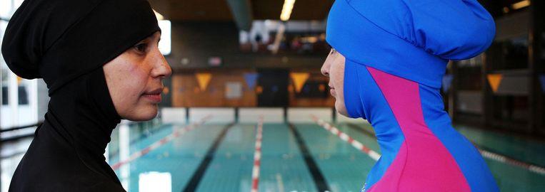 Vrouwen met boerkini's bij een zwembad. Beeld anp