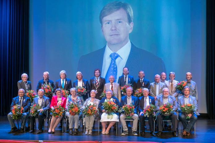 De gedecoreerden uit de gemeente Ede poseren na afloop van de ceremonie met burgemeester René Verhulst op het podium in De Reehorst.