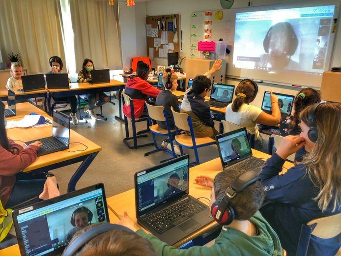 De kinderen in de klas met een laptop en koptelefoon. De juf thuis voor de webcam.