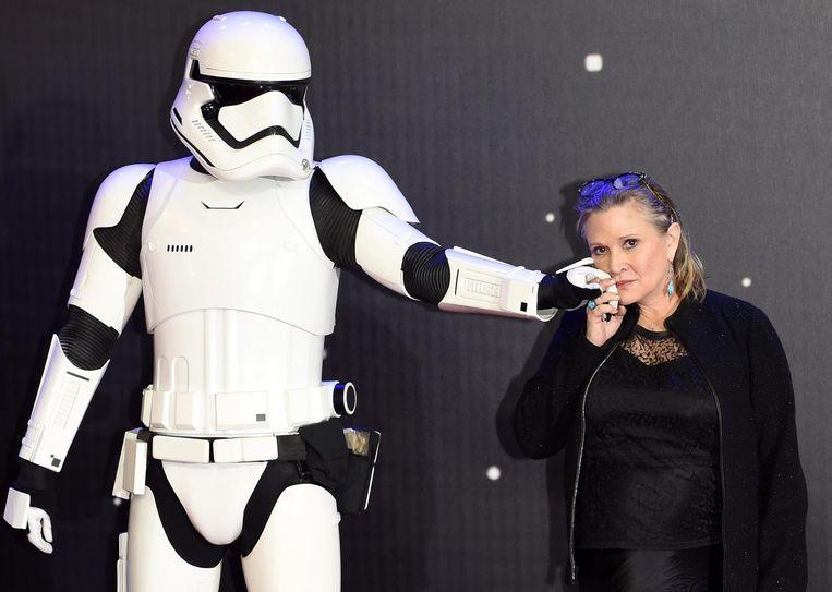 Carrie Fisher met een Stormtrooper bij de première van Star Wars: The Force Awakens. Beeld epa