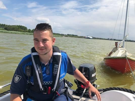 Boa Rik van den Heiligenberg aan het roer van de patrouilleboot met aan de sleeplijn het zeilbootje van Ferry en zijn zoon Sasha Rast.