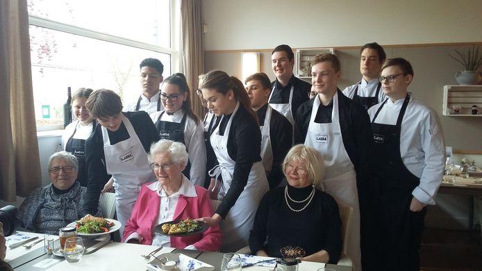 Riet Kruitbosch (in roze jas) die dertig jaar bij het schoolrestaurant van Pontes in Goes dineert.