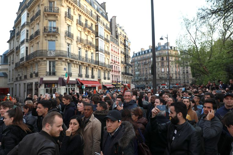 Mensen kijken toe terwijl de Notre Dame in brand staat. Beeld Getty Images