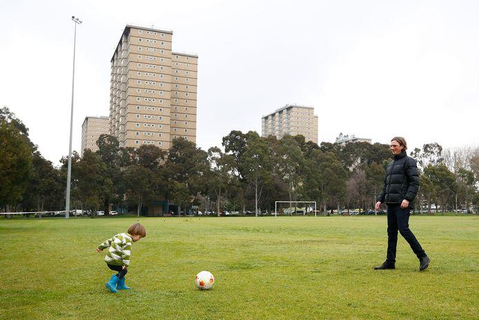 Een vader speelt met zijn kind, op de achtergrond enkele van de woontorens.