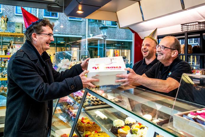 Links Martin Blokland, die de taart ophaalt bij vader en zoon Wammes.