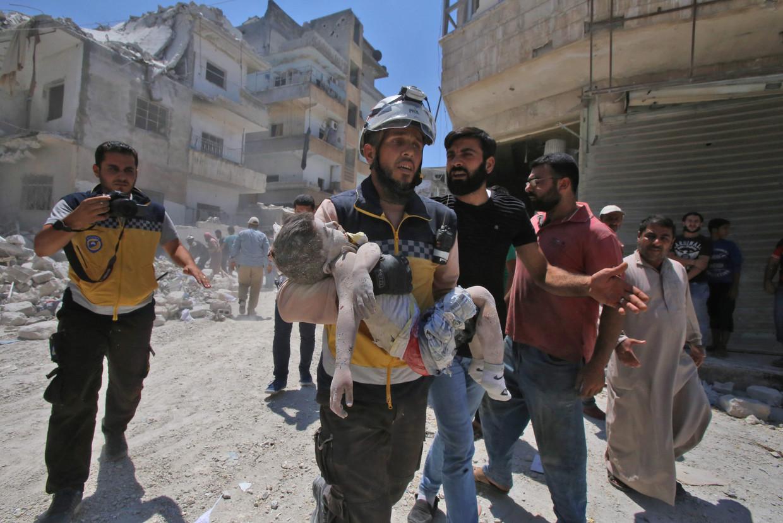 Een lid van de Witte Helmen draagt het lichaam van een kind in Ariha, in het zuiden van Idlib, na een luchtaanval. Beeld AFP