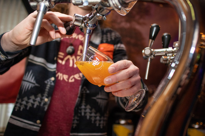Gijs Startman van Brouwerij de Hemel schenkt speciaalbier tijdens de wintereditie van de Nijmeegse bierfeesten in het Kolpinghuis.