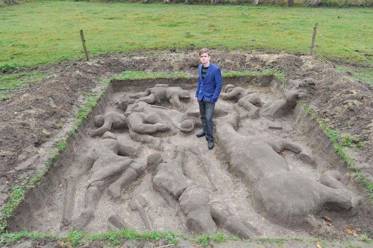 Rob Buelens bij zijn moddersculptuur ' No Man's Land ' in zijn tuin in Londerzeel. Daarvan wil hij volgend jaar een grotere versie maken in Ieper. Om daarvoor geld in te zamelen, verkoopt hij kleine oorlogstaferelen uit klei (inzet boven).