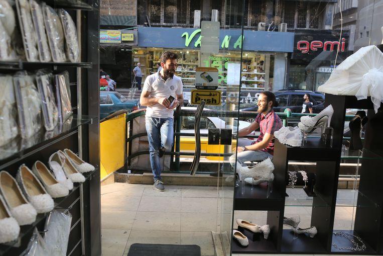 Anas Mohamed (l), parfumverkoper, maakt tijdens de pauze graag een praatje met andere Syrische vluchtelingen die in deze goede buurt van Cairo winkeltjes hebben.  Beeld Asmaa Waguih
