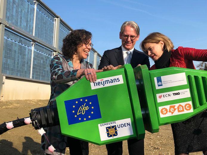 Minister Cora van Nieuwenhuizen (rechts) steekt met TNO-voorman Ton de Jong en Heleen Herbert van Heijmans de stekker in de 'groene geluidswal' bij Uden.