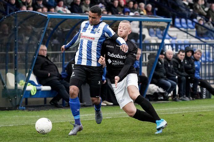 Beeld uit de wedstrijd tussen Quick Boys en GVVV. Niek Oosterlee (op achtergrond) ziet hoe Tom Oostinjen het in gaat.