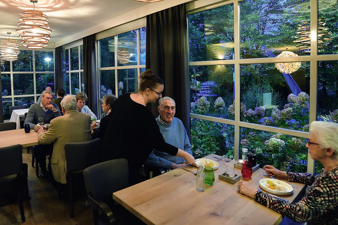 Gastvrouw Laura van Gaal aan tafel bij haar klanten.