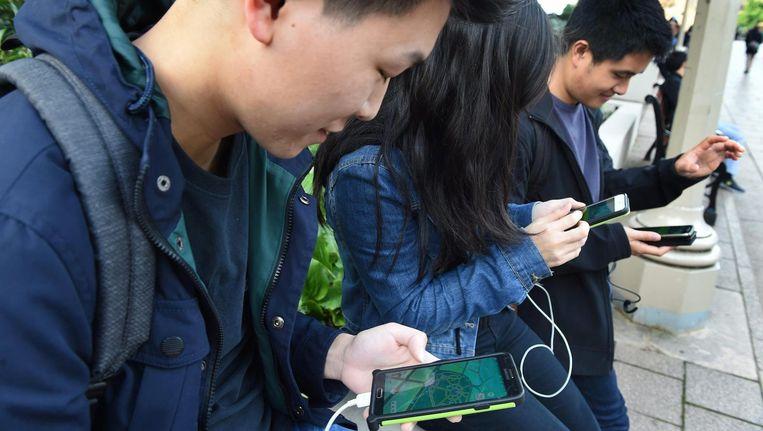 Jongeren spelen het spelletje op hun smartphone. Beeld anp
