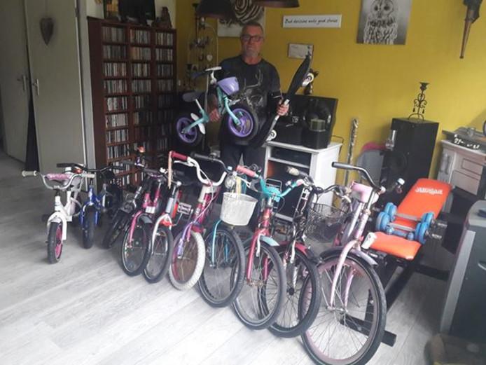 De huiskamer van Jan Kooijman stond vol met fietsen. Samen met Mans Semler (hier op de foto) repareert hij de fietsjes.