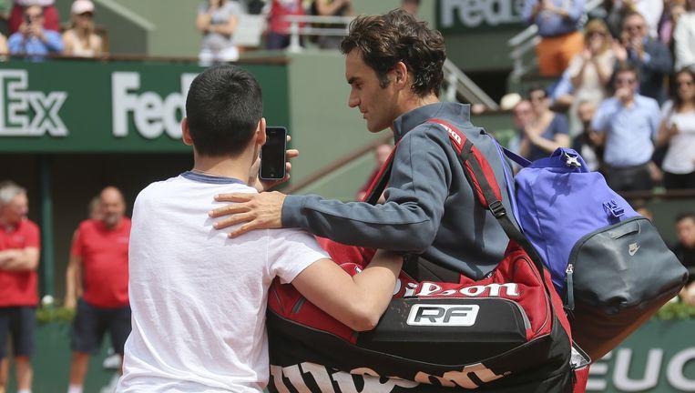 Een fan is de baan opgelopen om een selfie te maken met Federer. De tennisser vergeleek het met een inbraak in zijn huiskamer. Beeld AP