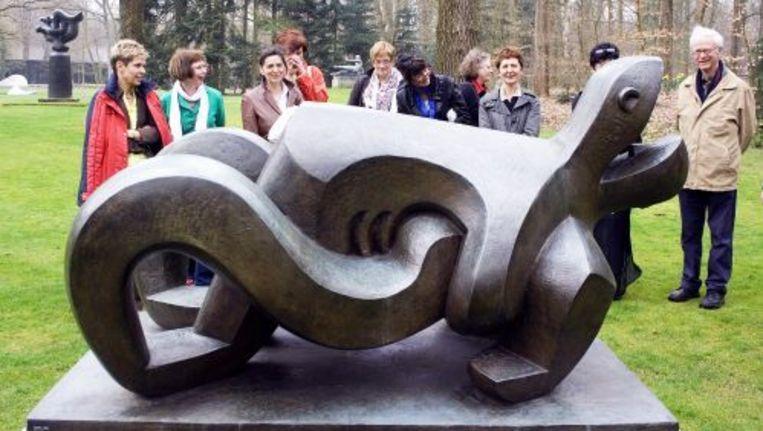 Dagjesmensen bekijken het beeld Le Cri van Jacques Lipchitz in de tuin van het Kroller-Moller museum in Otterlo. Foto ANP Beeld