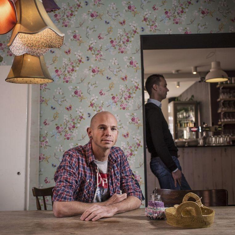 Arnoud de Rooij in zijn vegetarisch restaurant 'Van De Buurt' in de Bos en Lommer. Op de achtergrond zijn man Joghem de Gram. Beeld Marc Driessen