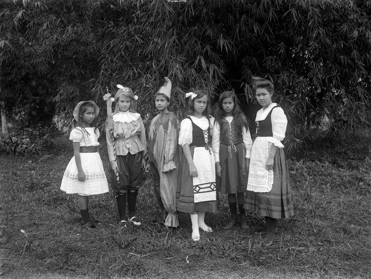 Een groep Europese en Indonesische meisjes, in toneelkleren, in de tuin van de Ursulinenschool in Bandoeng, Java (1880-1910).  Beeld Hollandse Hoogte / Spaarnestad P