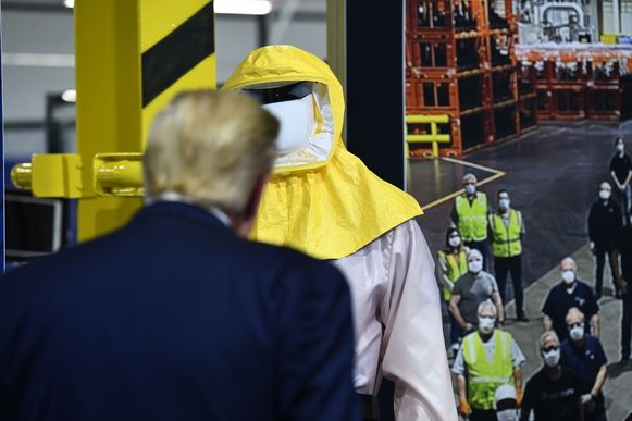 In de Ford-fabriek in Ypsilanti (Michigan) is het dragen van mondmaskers verplicht.  Aanwezige fabrieksarbeiders kijken toe hoe Trump een etalagepop met beschermende kledij inspecteert.