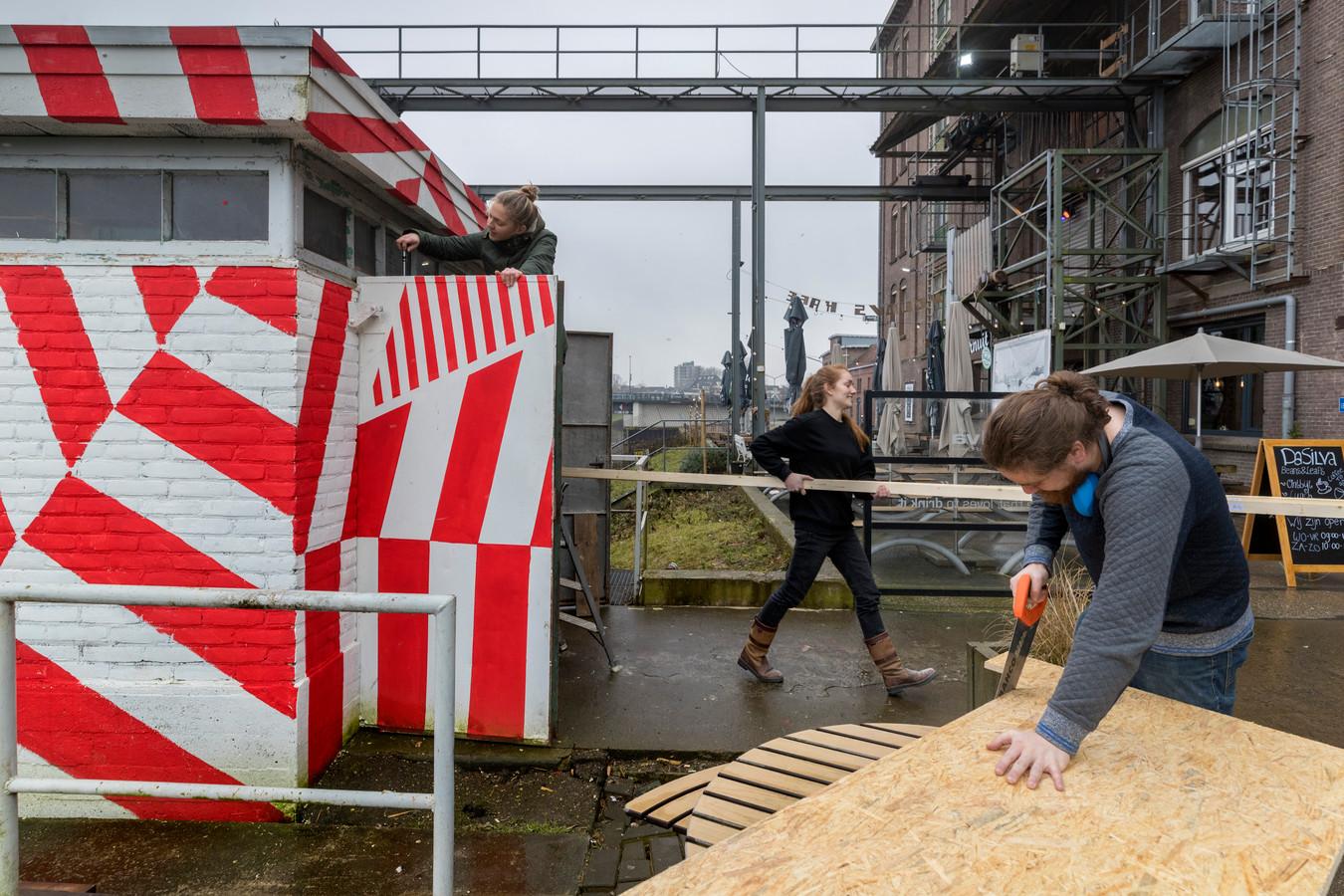 Het brandweerhuisje wordt opgeknapt door links op de trap Lizette van Dijk, met palen Anne Reijnders en zagend Jorn van Hoof.