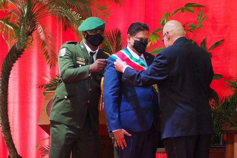 De nieuwe president van Suriname, Chan Santokhi, ontvangt de presidentiële sjerp tijdens zijn inauguratie. Beeld AP