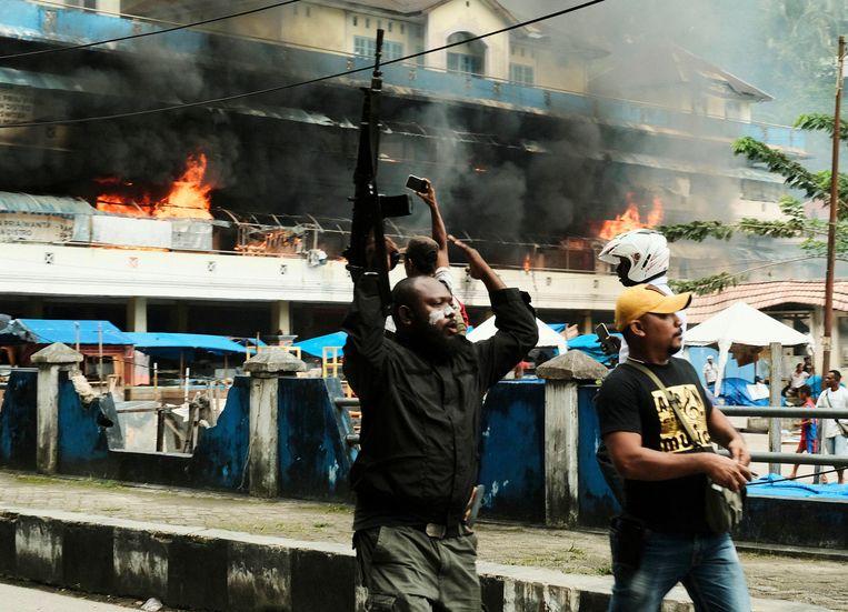 Papoea's ontvluchten de markt in de havenstad Fakfak, nadat bij een betoging de markthal in brand is gestoken. De demonstratie vond eind augustus plaats. Beeld AP