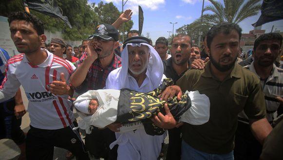 Inwoners van Gaza dragen de drie jaar oude Muayyad al-Araj ten grave. De peuter kwam gisteren om het leven bij een Israelische luchtaanval.
