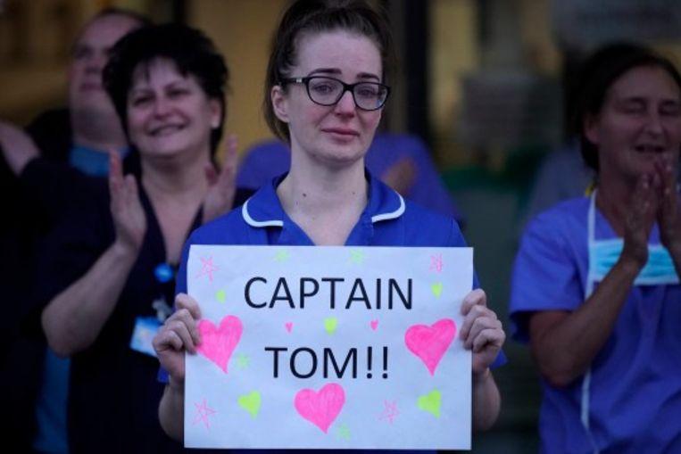 Zorgverleners reageren juichend op de aandoenlijke actie van Moore. Beeld Getty Images