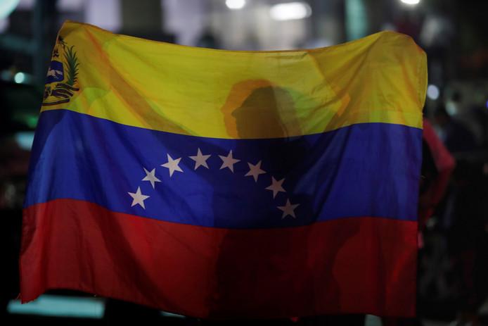Een vrouw met een Venezolaanse vlag tijdens een stille tocht voor de slachtoffers van recent geweld in hoofdstad Caracas begin mei. Foto ter illustratie.