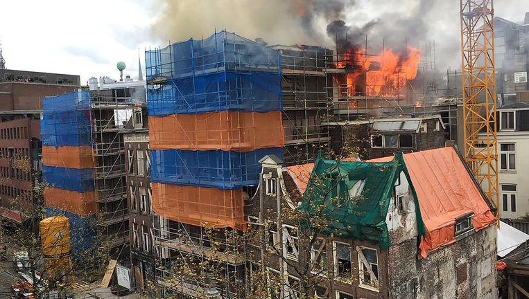 Grote vlammen slaan zaterdagmiddag uit het dak van panden in de Wijdesteeg. Beeld Marc Postma