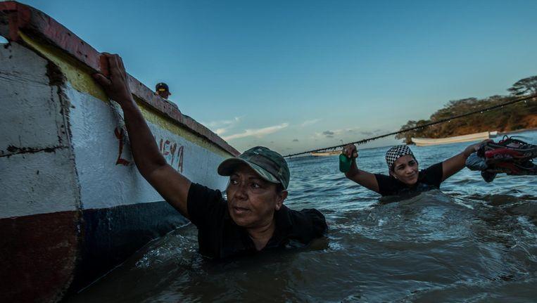 Maria Piñero (links) en Andrea Gomez waden naar de boot die hen naar Curaçao moet brengen. Beeld Meridith Kohut, The New York Times
