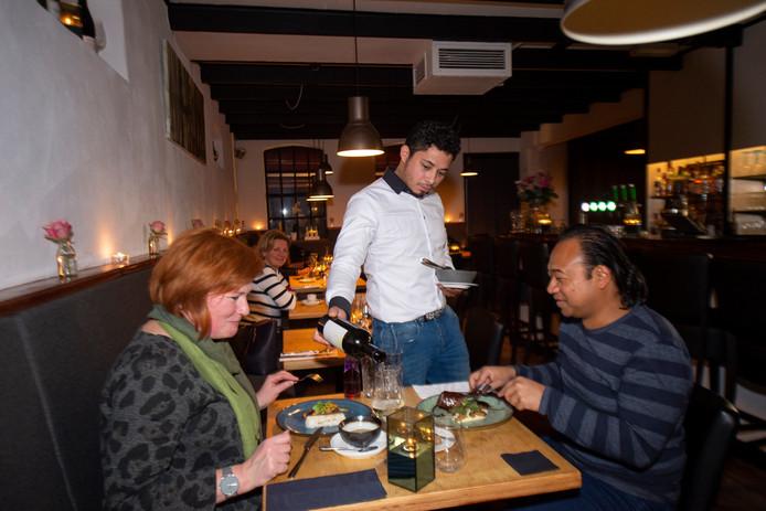 Restaurantrubriek Over de Tong at bij Gastrobar Base in Apeldoorn. Mede-eigenaar Juan Holtrigter schenkt deze gasten een bijpassende wijn. Tessa en Janske hadden overigens een andere gastheer zaterdagavond.