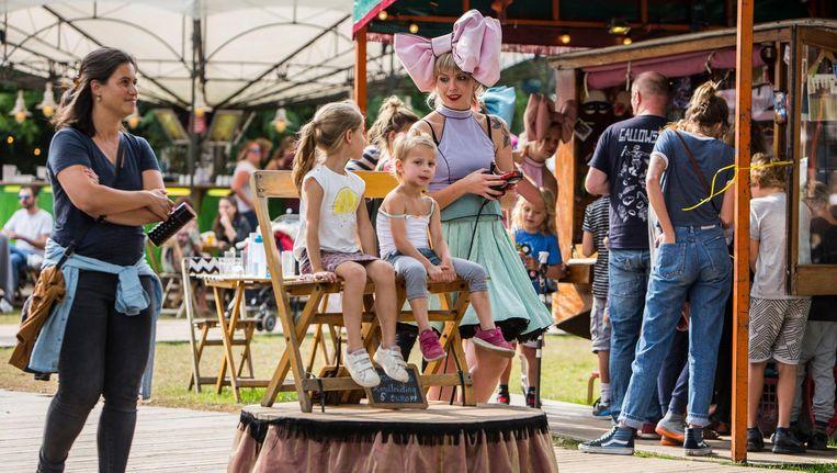 Een snoepmeisje geeft een rondleiding op het festivalterrein. Beeld Amaury Miller