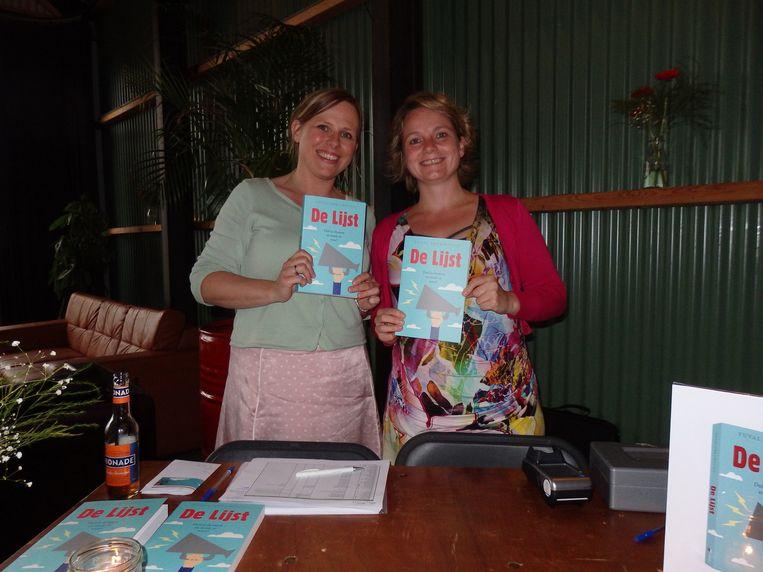 Annelies Nijboer (l) en Maaike Dijkstra van Kosmos Uitgevers verkopen boeken, gesigneerd. Beeld Schuim