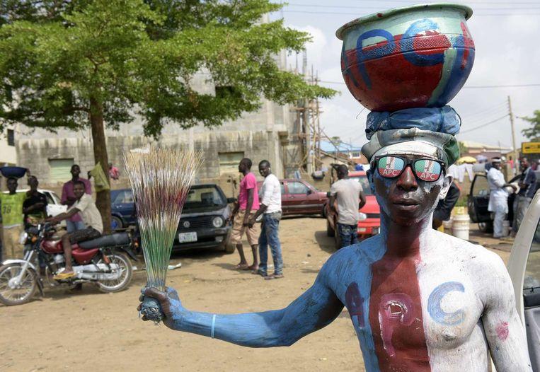 Een man in kleuren van de grootste oppositiepartij APC, onder leiding van Muhammadu Buhari. De verkiezingen van dit jaar zijn de spannendste in de historie van Nigeria. Beeld afp