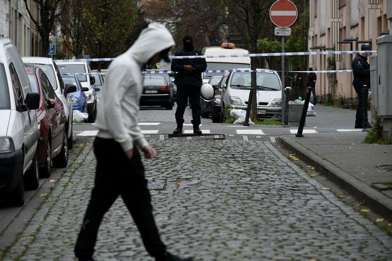Een jongeman passeert een afgezette straat in Molenbeek. Beeld anp