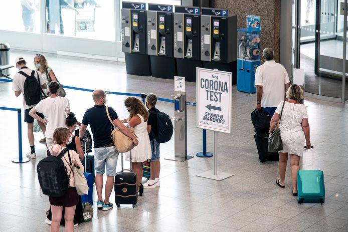 Reizigers uit Ibiza, zojuist geland op de luchthaven Weeze, staan in de rij voor de test.