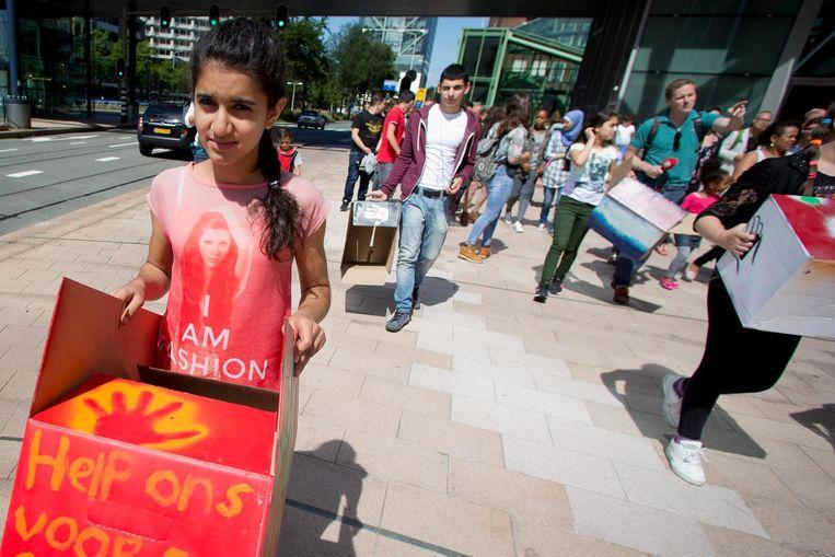 Asielzoekers en hun kinderen lopen in 2015 in een protestmars vanaf Den Haag Centraal naar de rechtbank waar een kort geding dient tegen het Centraal Orgaan opvang Asielzoekers (COA). Beeld anp