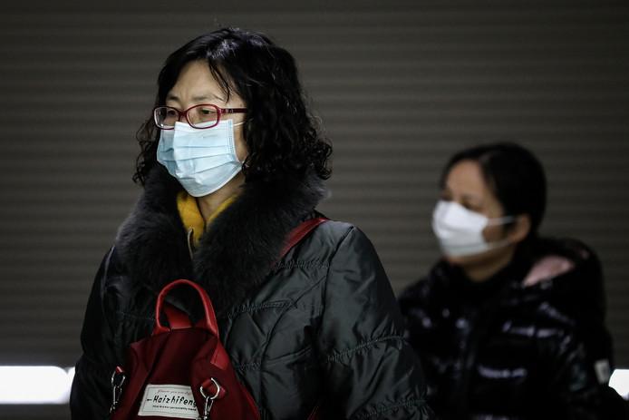 Een Chinese vrouw draagt een mondkapje ter bescherming tegen het in Wuhan opgedoken virus.