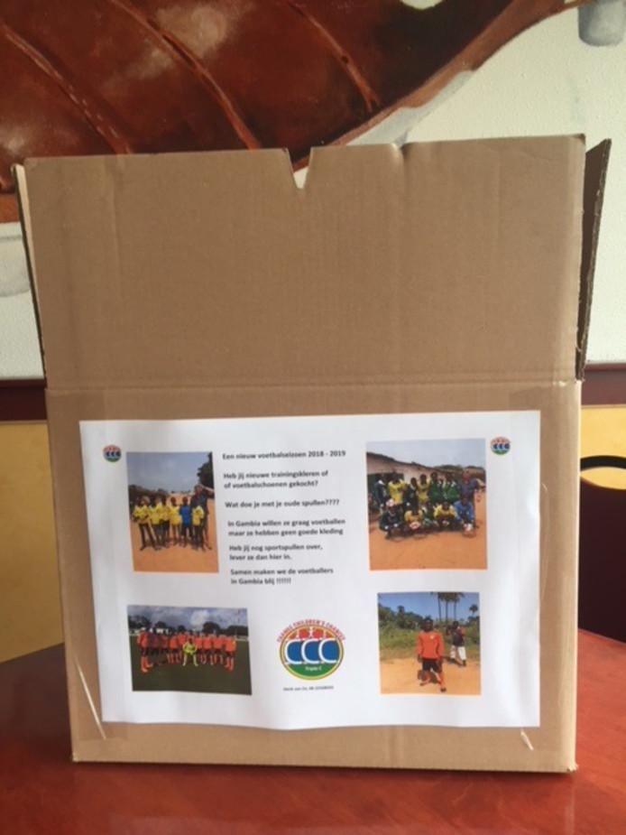 Een doos waarin de kleding voor Gambia wordt verzameld in de voetbalkantines.