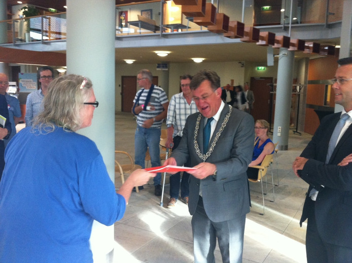 Burgemeester Hellegers heeft zojuist uit handen van Genoveef Lukassen de rode map met 290 proteststemmen tegen het foodcourt in Uden ontvangen. Wethouder Peerenboom kijkt toe.