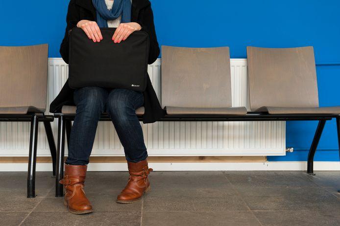Een jonge vrouw in de wachtkamer van het UWV.