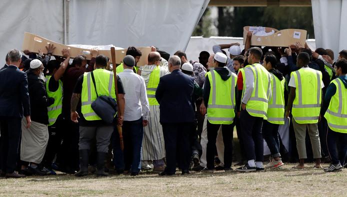 De lichamen van vader en zoon Khaled en Hamza Mustafa worden door rouwende mensen naar het Memorial Park Cemetery in Christchurch gedragen.