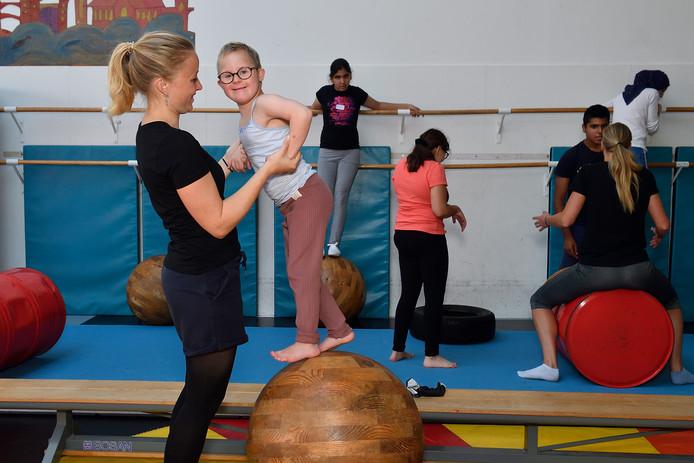 Lieve probeert zich, met hulp van een medewerkster van de Circusschool, staande te houden op een houten bal.
