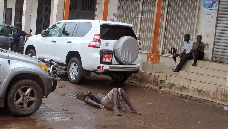 De politie houdt de wacht bij een doodzieke man die in Guinee op straat ligt. Beeld AP
