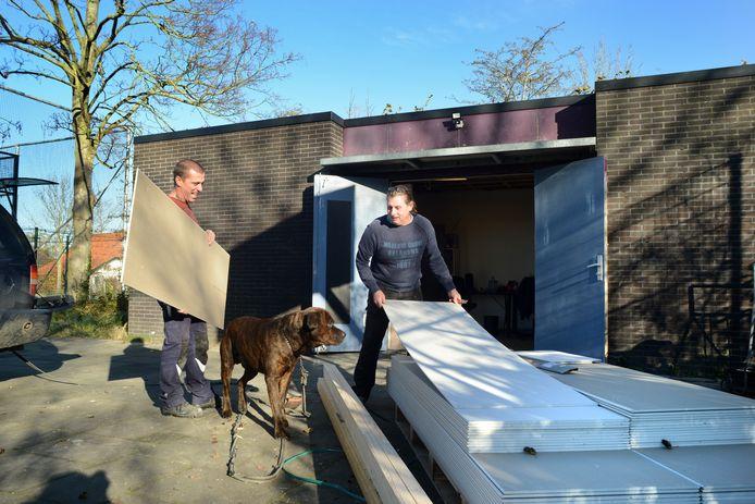 Erik de Vries (r) en Marcel de Bruijn in de weer met gipsplaten voor het nieuwe, geïsoleerde plafond in het voormalige jeugdhonk van Scharendijke. Hond Marley houdt een oogje in het zeil.