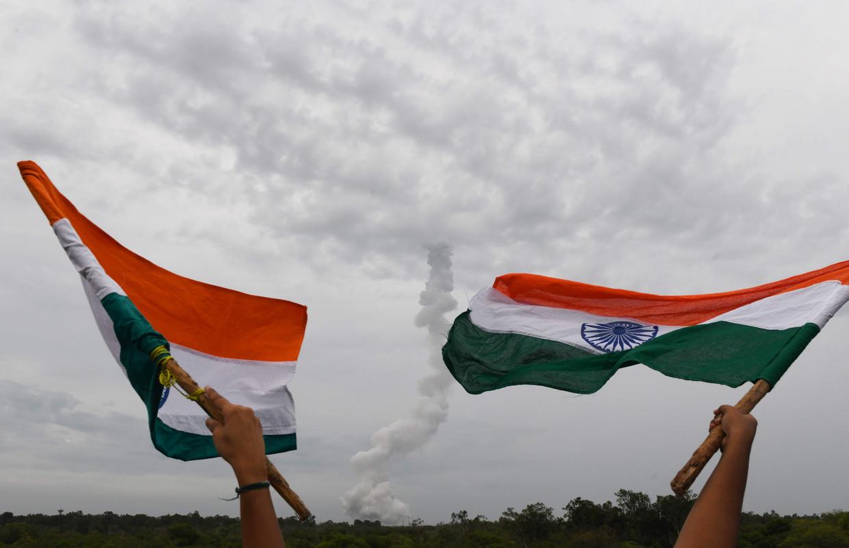 Toeschouwers wapperen met de Indiase vlag, met op de achtergrond het rookspoor van de Chandrayaan-2-missie, die een lander op de zuidpool van de maan moet zetten.