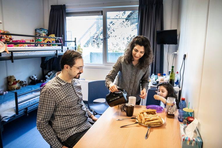Enes en Elaheh Akin met hun dochter. Door tekorten bij de IND wachten ze al maanden op hun eerste gesprek bij de IND.  Beeld Koen Verheijden