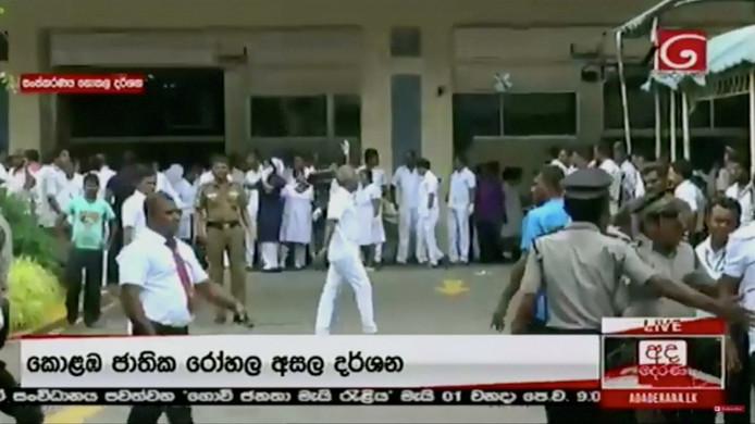 Mensen wachten buiten een ziekenhuis op nieuws.
