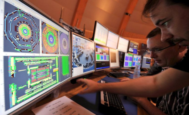 Wetenschappers in het CERN aan computerschermen van het Atlas-experiment. Foto EPA/Fabrice Coffrini Beeld